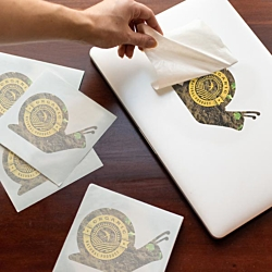 Snail decal being applied to a laptop with extra decals waiting nearby.