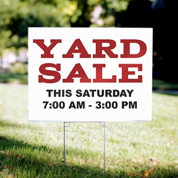 Corrugated plastic yard sign installed on a stake in a yard with printed content advertising a yard sale and a date and time.